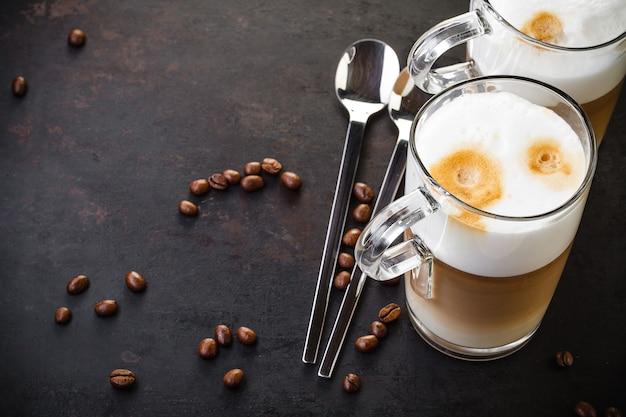 Zwei gläser latte ad löffel auf dunkel rustikal