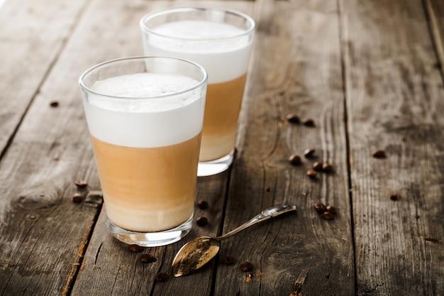 Zwei gläser latte kaffeebohnen und löffel om pld holztisch.