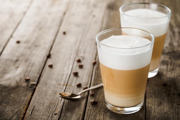 Zwei gläser lattekaffee mit bohnen und löffel auf altem holztisch.