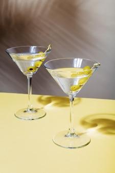 Zwei gläser martini-cocktails mit grünen oliven, auf dem hintergrund des schattens tropischer pflanzen