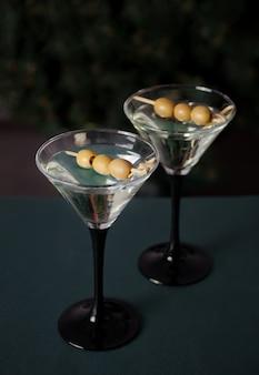 Zwei gläser martini mit oliven auf der dunkelheit.
