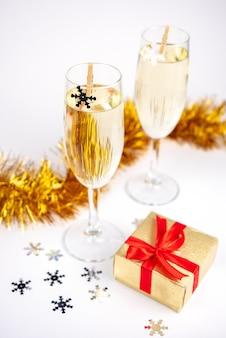 Zwei gläser mit champagner, goldener geschenkbox und weihnachtsdekoration mit schneeflocken