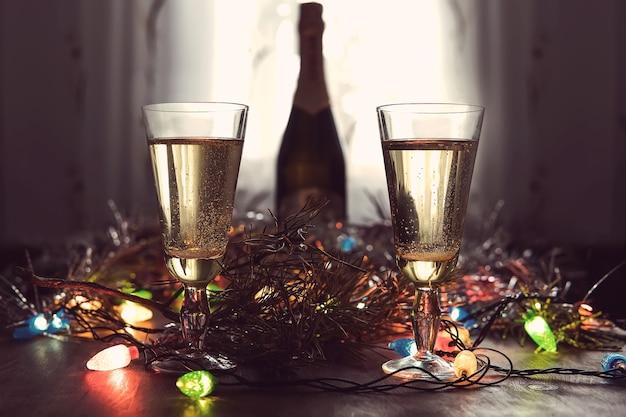 Zwei gläser mit champagner und flasche auf einem mit weihnachtsaccessoires dekorierten holztisch, um das neue jahr und weihnachten zu feiern. romantischer abend. das leuchten der girlanden. valentinstag