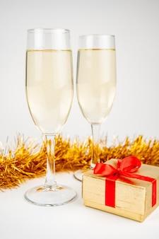 Zwei gläser mit champagner und goldener geschenkbox