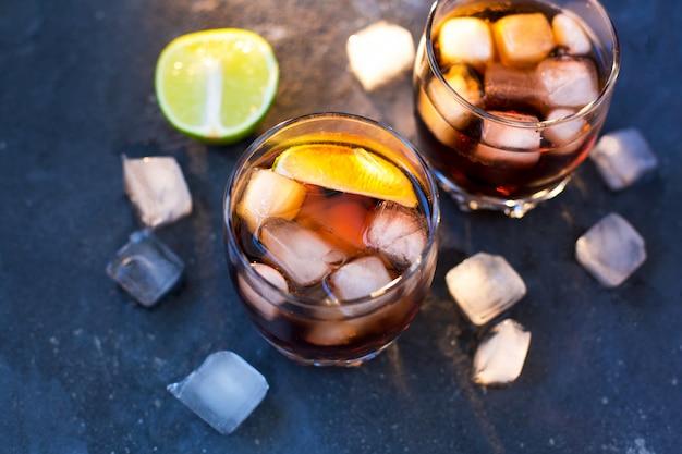 Zwei gläser mit cocktails: rum cola und cola whisky stehen auf einem graublauen strukturierten betonhintergrund und eiswürfel und gehackte limette liegen herum