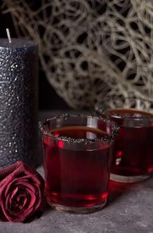 Zwei gläser mit dem roten cocktail, getrocknet stiegen für halloween-party auf dunkelheit
