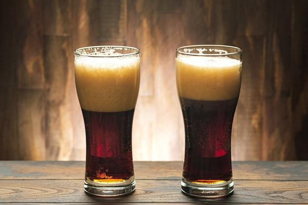 Zwei gläser mit dunklem bier und schaum