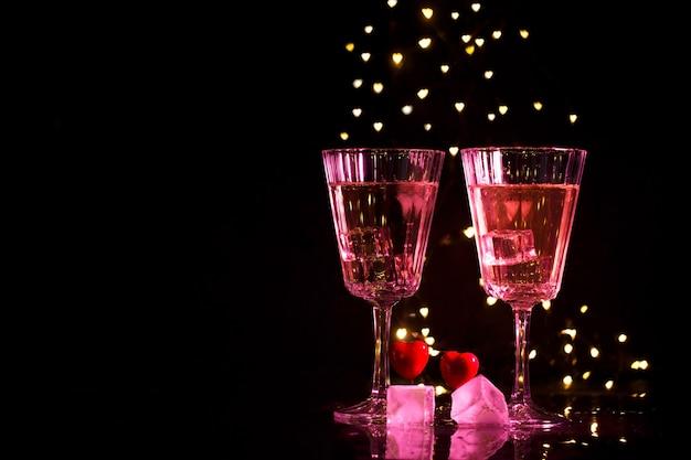 Zwei gläser mit einem cocktail und zwei herzen, valentinstagkonzept.