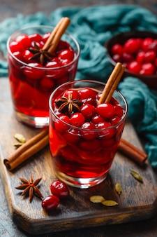 Zwei gläser mit einem heißen getränk aus preiselbeeren und äpfeln mit gewürzen, glühwein, punsch oder grog.