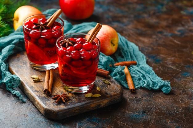 Zwei gläser mit einem heißen weihnachtsgetränk aus preiselbeeren und äpfeln mit gewürzen, glühwein, punsch oder grog.