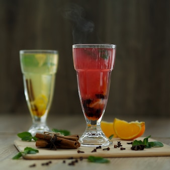 Zwei gläser mit farbigen heißgetränken, aus denen dampf kommt. winter heiße saisonale getränke