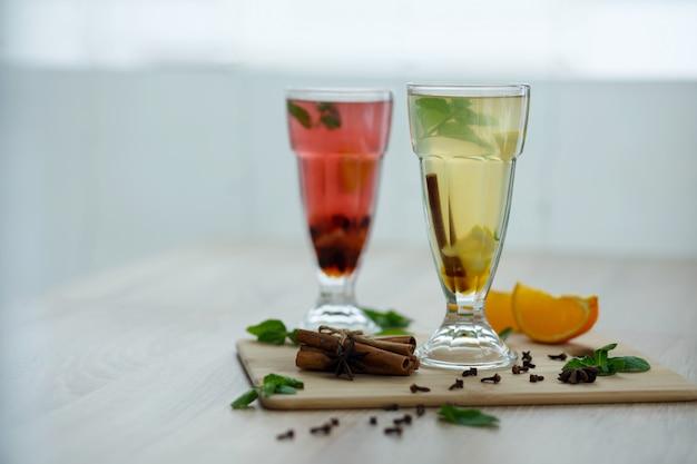 Zwei gläser mit farbigen heißgetränken, aus denen dampf kommt. winter heiße saisonale vitemin getränke