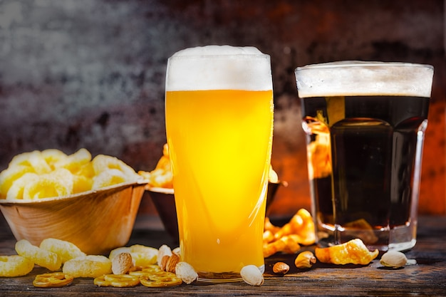 Zwei gläser mit frisch gegossenem, hellem, ungefiltertem und dunklem bier in der nähe von tellern mit pommes und verstreuten snacks auf einem dunklen holzschreibtisch. lebensmittel- und getränkekonzept