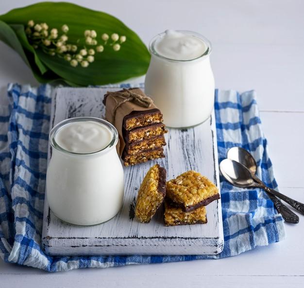 Zwei gläser mit hausgemachtem joghurt und snacks aus müsli