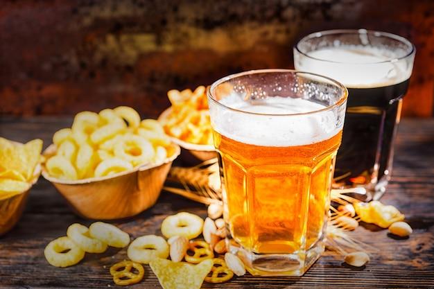 Zwei gläser mit hellem und dunklem bier in der nähe von tellern mit pommes und verstreuten snacks auf einem dunklen holzschreibtisch. lebensmittel- und getränkekonzept