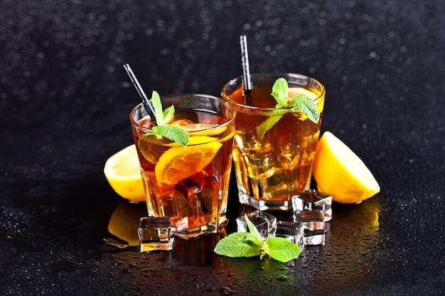 Zwei gläser mit kaltem traditionellem eistee mit zitrone, tadellosen blättern und eiswürfeln.