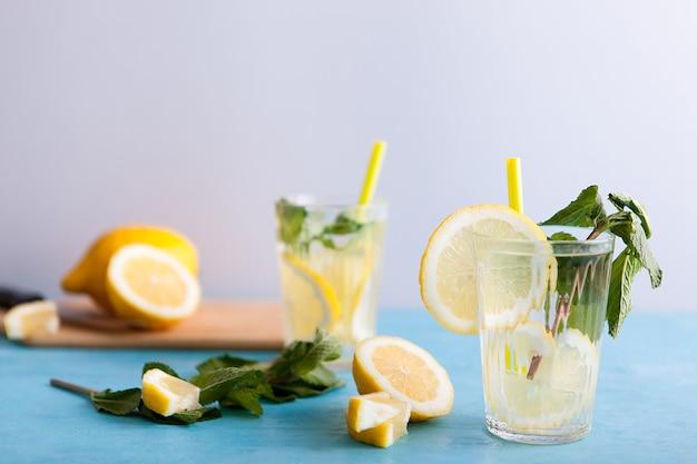 Zwei gläser mit köstlicher hausgemachter limonade auf grauem hintergrund auf blauem schreibtisch sitzend