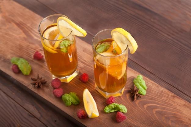 Zwei gläser mit kombucha, trinkhalmen und zitronenscheiben, himbeeren stehen auf einem holztisch. gesundes lebensmittelkonzept.