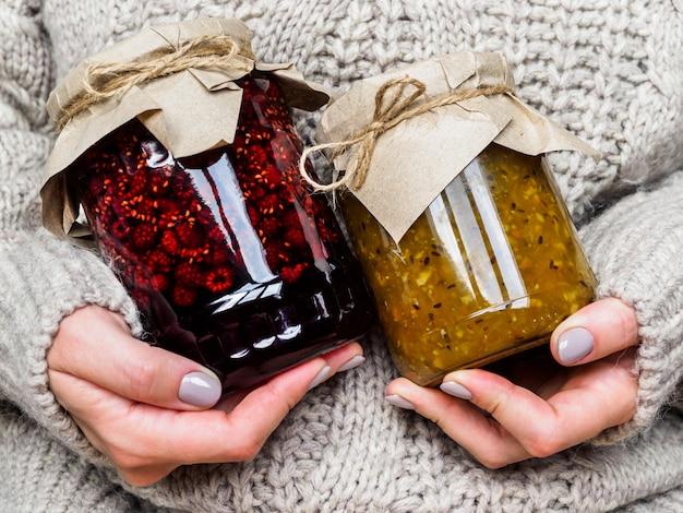 Zwei gläser mit marmelade in den händen eines mädchens