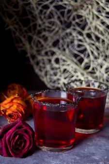 Zwei gläser mit rotem cocktail, getrocknete rosen für halloween-party auf dunkelheit