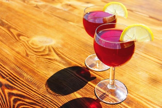 Zwei gläser mit roten sommercocktails mit zitronenscheiben auf holzhintergrund.