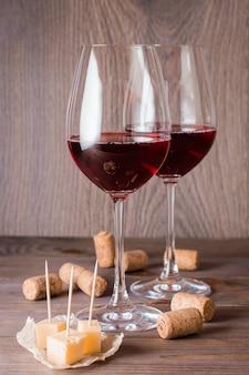 Zwei gläser mit rotwein, stücken käse und korken auf einem holztisch