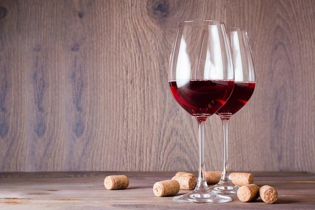 Zwei gläser mit rotwein und korken auf einem holztisch