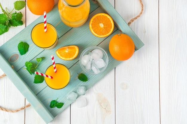 Zwei gläser mit saft und tuben, orangen, minze und eiswürfeln auf einem brett auf einem hellen schreibtisch. draufsicht mit kopierraum.