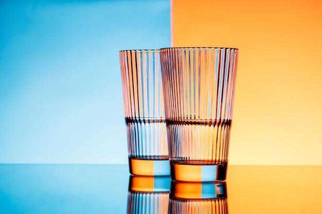 Zwei gläser mit wasser über blauem und orange hintergrund.