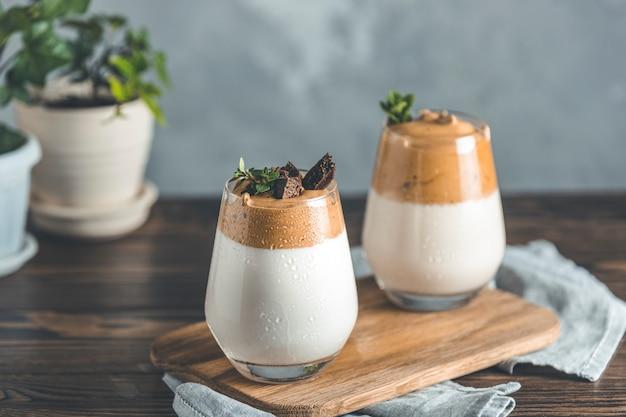 Zwei gläser mit wassertropfen dalgona schaumigen kaffeetrends koreanisches getränk latte espresso mit kaffeeschaum
