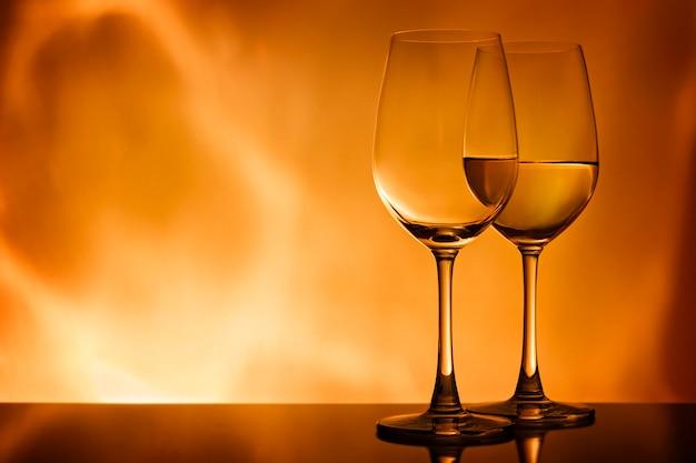 Zwei gläser mit weißwein auf einem orangefarbenen hintergrund