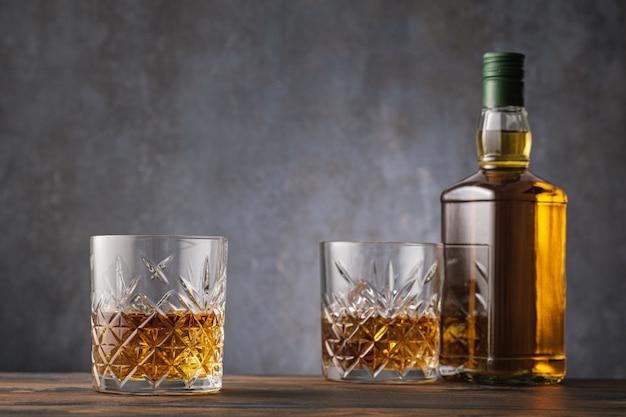 Zwei gläser mit whisky und alkoholflasche