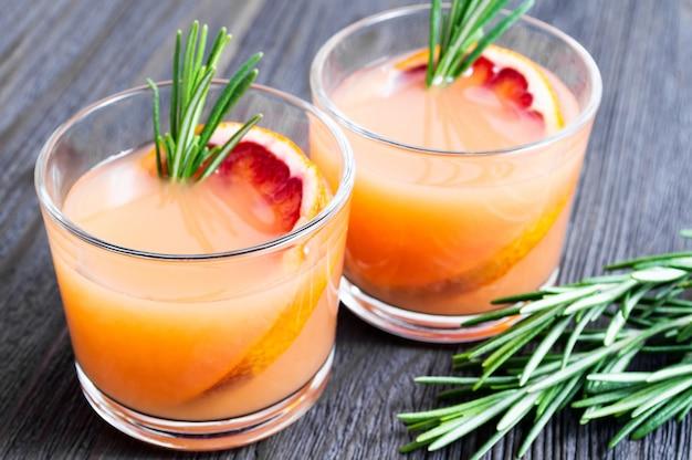 Zwei gläser neuer sommer trinken mit blutorange und rosmarin auf einem dunklen hölzernen hintergrund