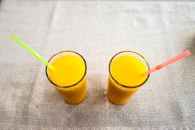 Zwei gläser orangensaft auf sackleinenhintergrund. gesundes getränk.