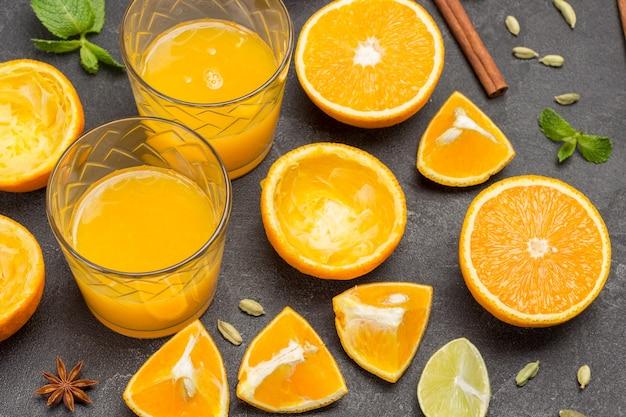 Zwei gläser orangensaft. gehackte orangen auf dem tisch. schwarzer hintergrund. ansicht von oben