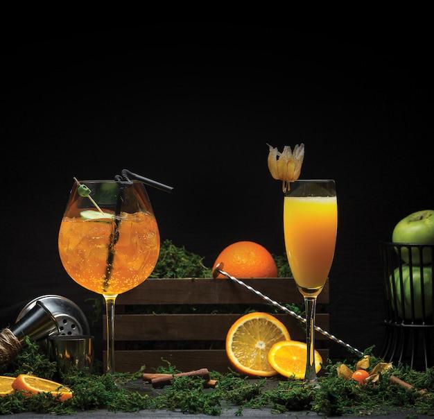 Zwei gläser orangensaft mit und ohne eiswürfel.