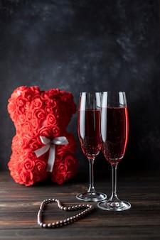 Zwei gläser roter champagner auf dunklem hintergrund, ein teddybär aus rosen. geschenk für frauen. frauenurlaub.
