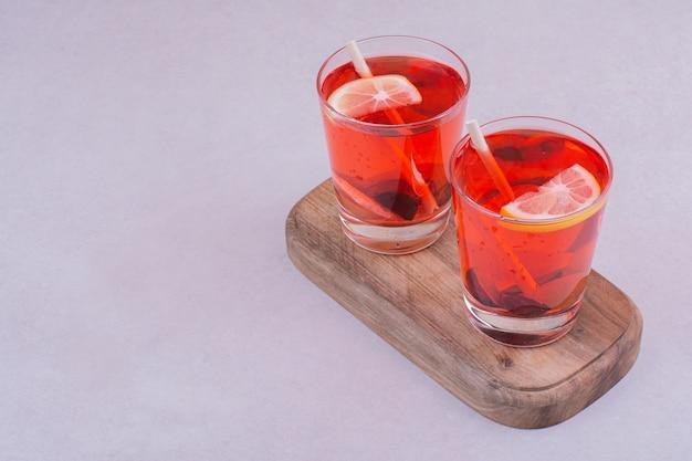 Zwei gläser roter saft auf einem holzbrett