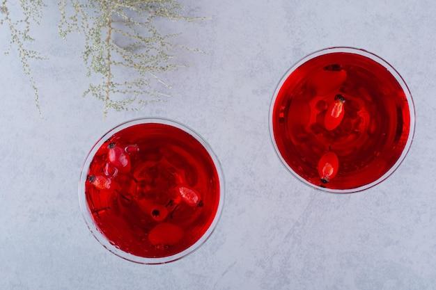 Zwei gläser roter saft auf stein