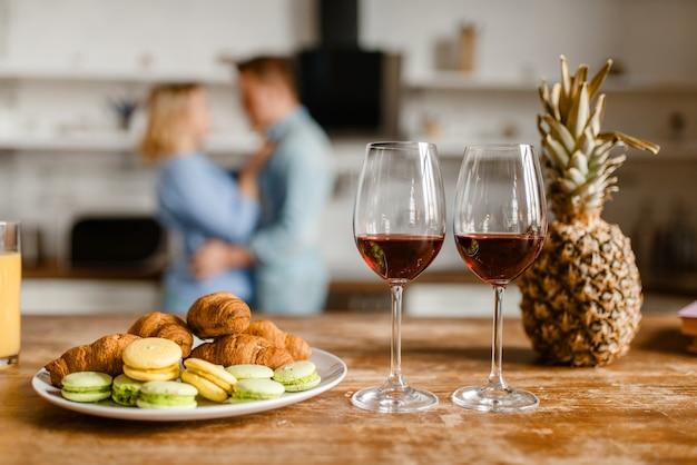 Zwei gläser rotwein auf dem tisch, liebespaar umarmt sich