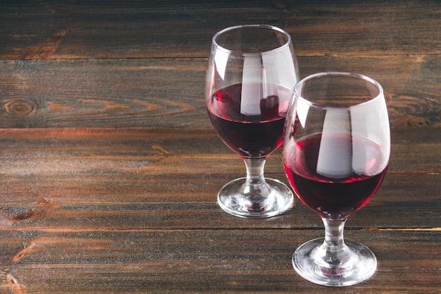 Zwei gläser rotwein auf einem braunen holztisch. alkoholische getränke.