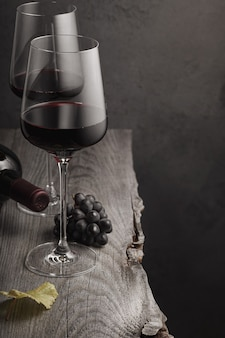Zwei gläser rotwein, eine flasche und trauben auf einem alten holztisch. dunkler hintergrund.