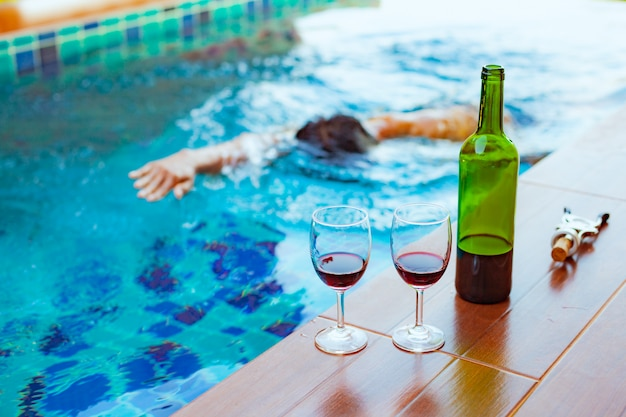 Zwei gläser rotwein nahe dem swimmingpool mit einem mann schwimmt im pool