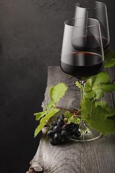 Zwei gläser rotwein, trauben und weinblätter auf einem alten holztisch. dunkler hintergrund.