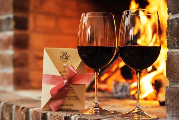 Zwei gläser rotwein und dekorative postkarte
