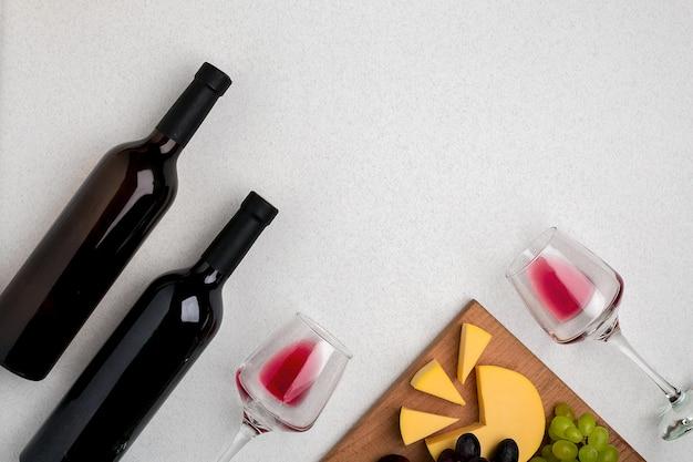 Zwei gläser rotweinkäse und trauben draufsicht