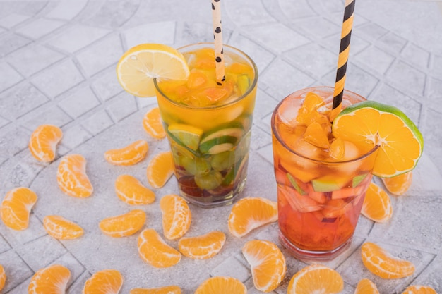 Zwei gläser saft mit fruchtscheiben auf marmoroberfläche.