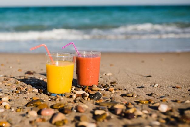Zwei gläser saft mit trinkhalm auf sandigem strand nahe der küste