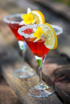 Zwei gläser sommercocktailgetränk verziert gelbe blume