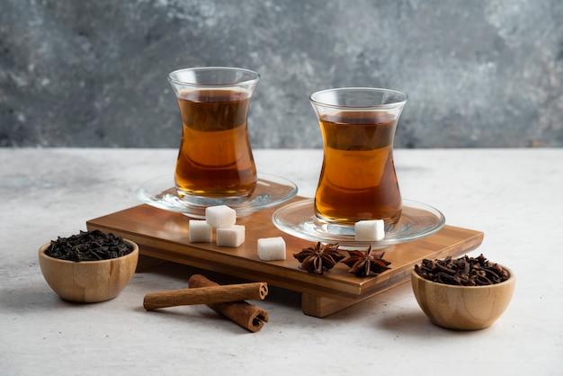 Zwei gläser tasse tee mit zucker und sternanis.